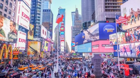 Times Square New York filled with people and huge billboards with ads