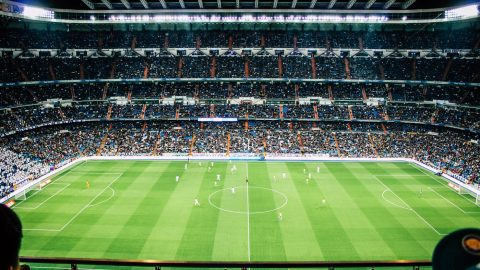 soccer stadium at night with a bright green field