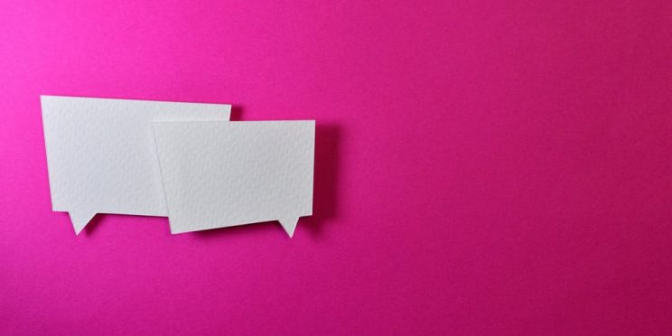 two white speech bubbles on a pink background