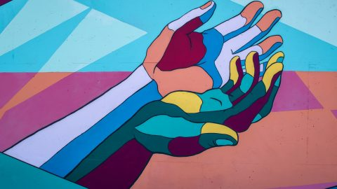Colourful abstract painting of open hands