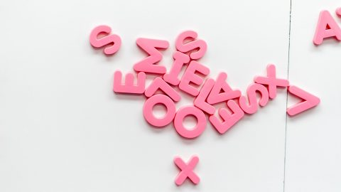 Pink plastic alphabet letters scattered across a table