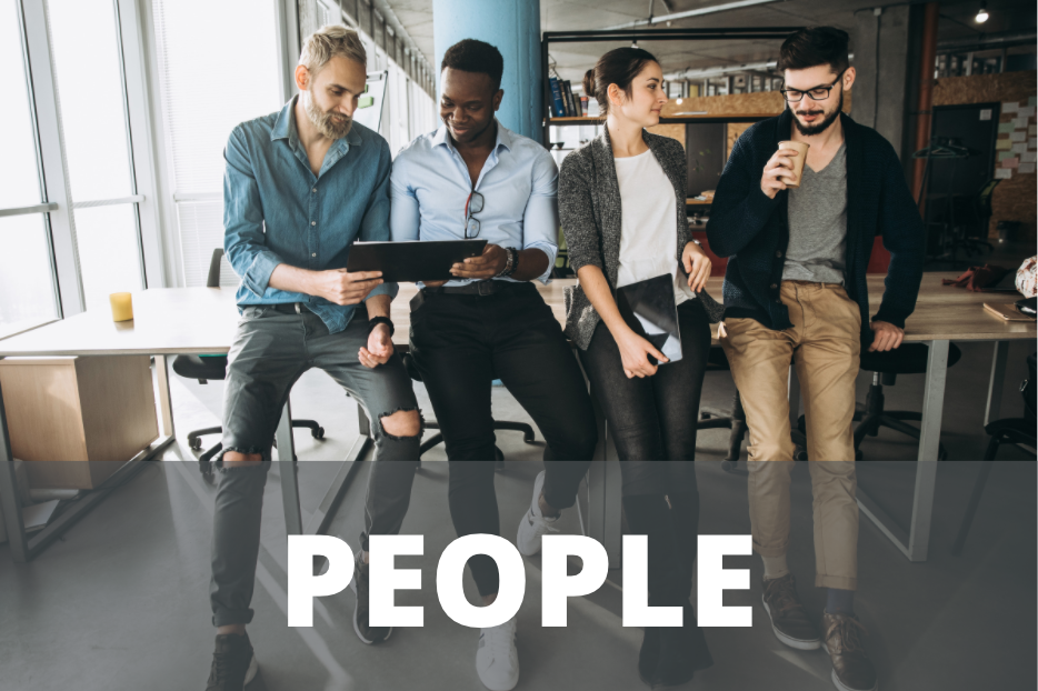 """four colleagues leaning against an office desk with the word """"people"""""""
