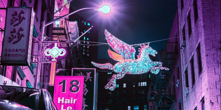 Light up unicorn hanging in amongst busy city nightlife
