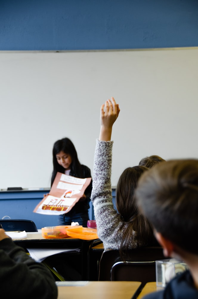 student raising their hand in class
