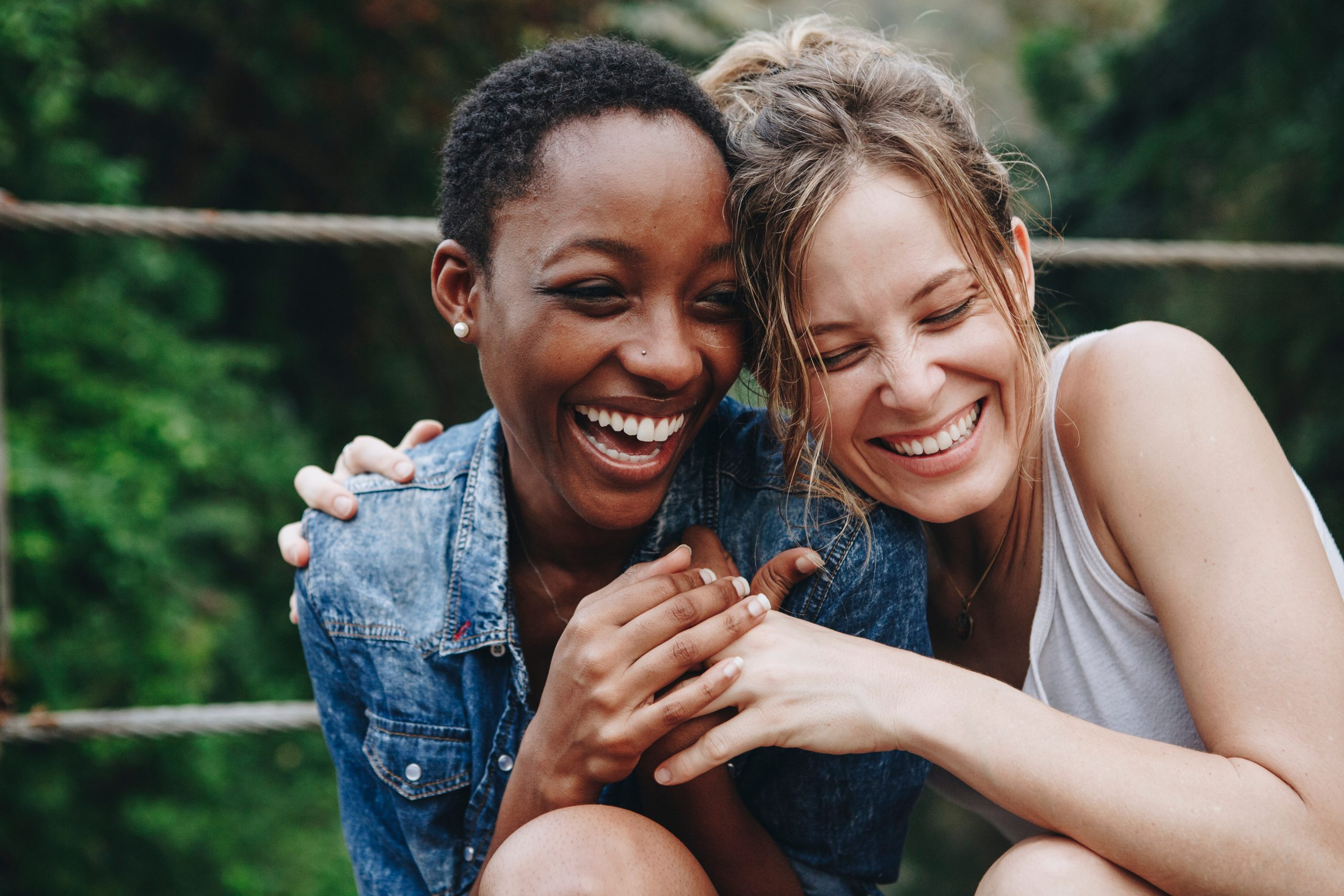 two women laughing and embracing