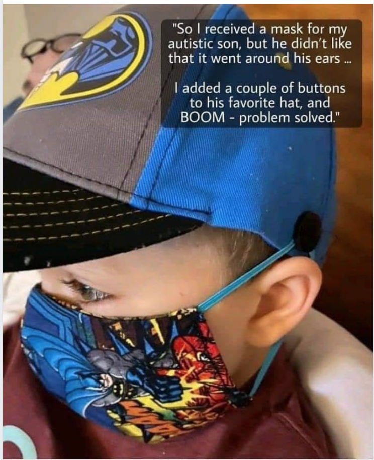 A boy with a mask and hat on. His mask is looped around buttons attached to his hat instead of his ears for comfort.
