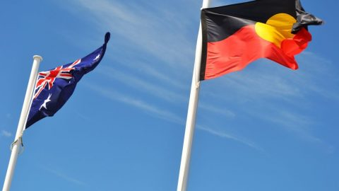 An Australian flag and Aboriginal flag flying side by side