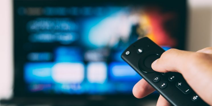 A remote control pointed at a flat screen television