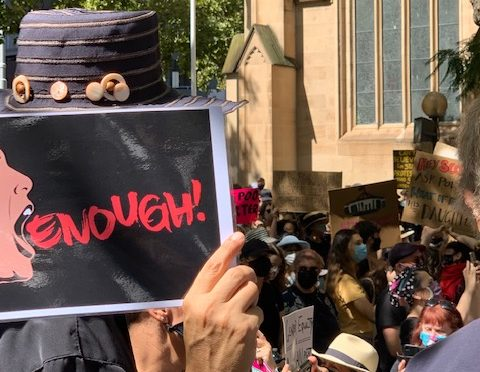 A sign in a crowd of people at a protest. It says 'enough'
