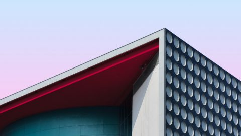 The corner of a building with a circle patterned side and blue face