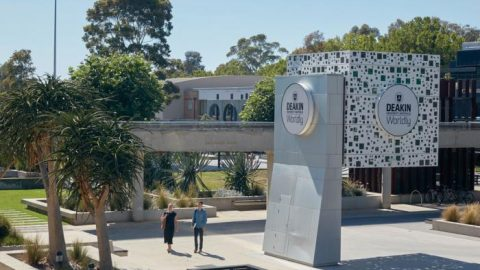 A Deakin University building set amongst trees, plants and students