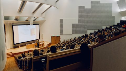 A modern lecture theatre full of students.