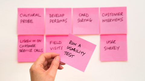 A pink post it note picked up out of a group of notes. It says run a usability test