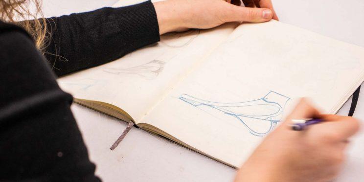 Eloise's hands seen sketching her design in a sketchbok